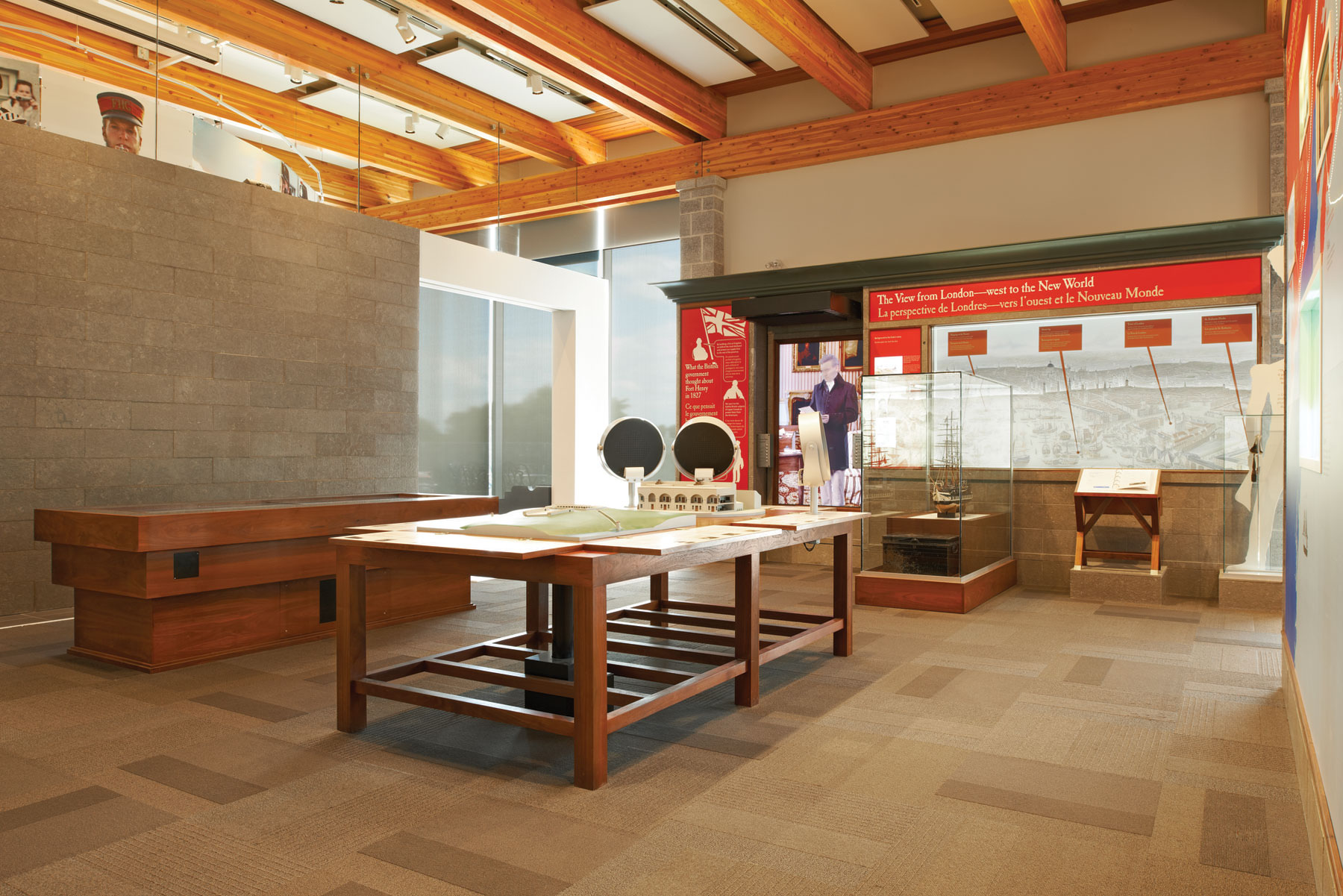 Exhibit space with floor and wall displays, stone wall on left and wood rafter ceilings