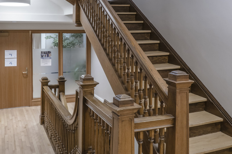 Large wood staircase connecting first, second and third floor with wood door and windows