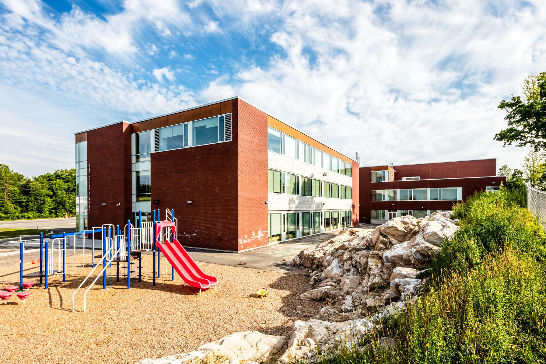 Three storey red brick school with glazed windows throughout with children's playground and natural rock barrier in foreground