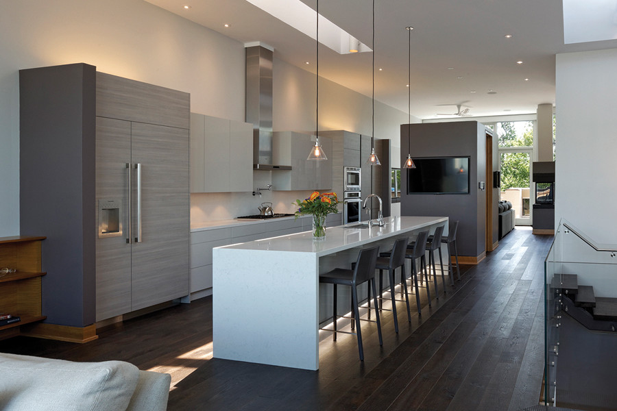 View from living room of kitchen with large white island with bar stools and pendant lighting