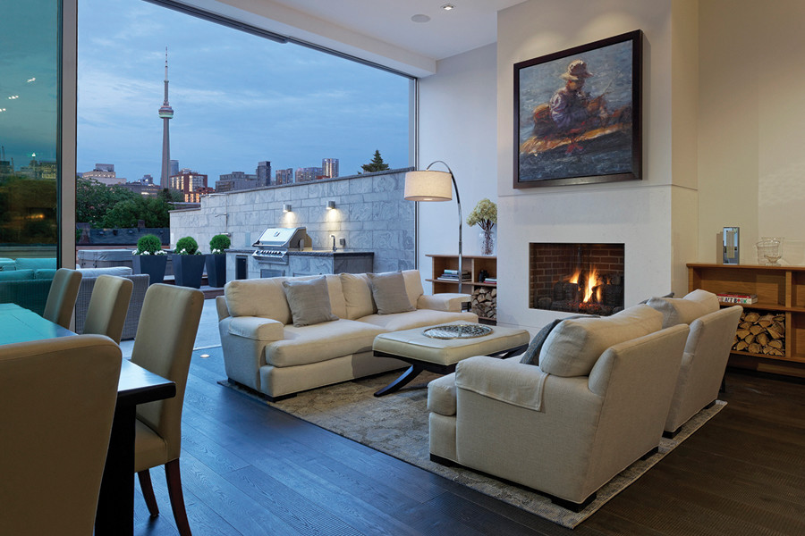 View of living room with fireplace and large white couches and large terrace with BBQ and views of trees and CN Tower at sunset