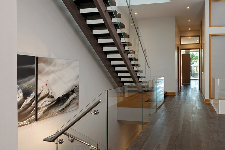 Open staircase with glass guard rail and corridor looking to front entrance and views up to second storey