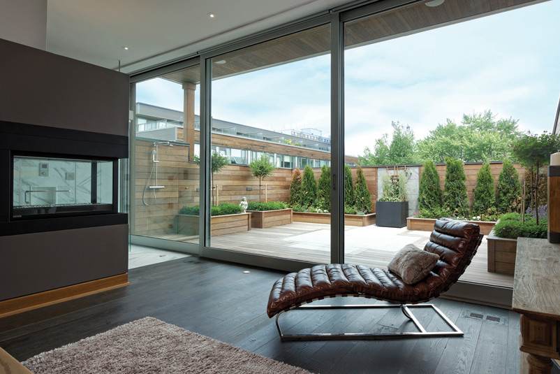 Lounge area with corner fireplace and large walled terrace with outdoor shower and cedar trees in planter boxes
