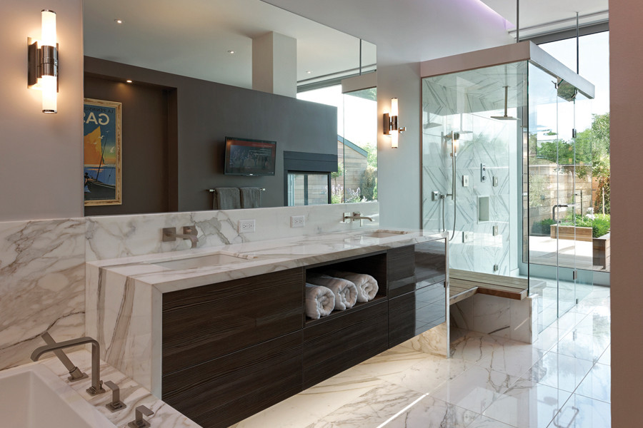 Marble bathroom with bathtub, double sink, scone lighting, and glass shower overlooking private walled terrace and trees