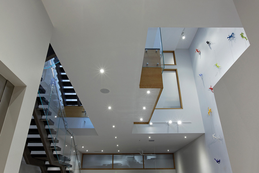 View from lower level with exposed staircases with glass guard rails on left and multi coloured action figures climbing the white walls on right