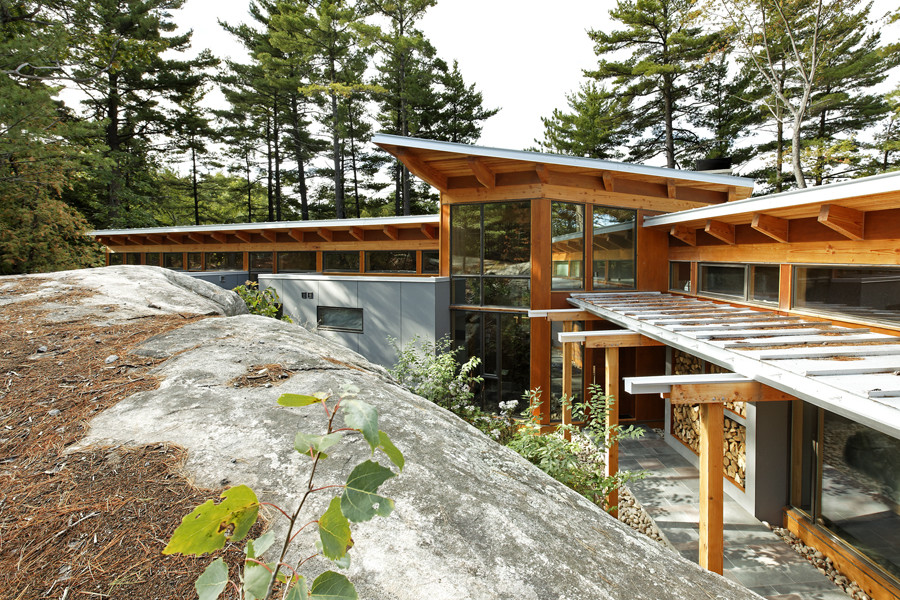 Elevation of wood and glass cottage featuring cantilever roof built into rock face and trees in background