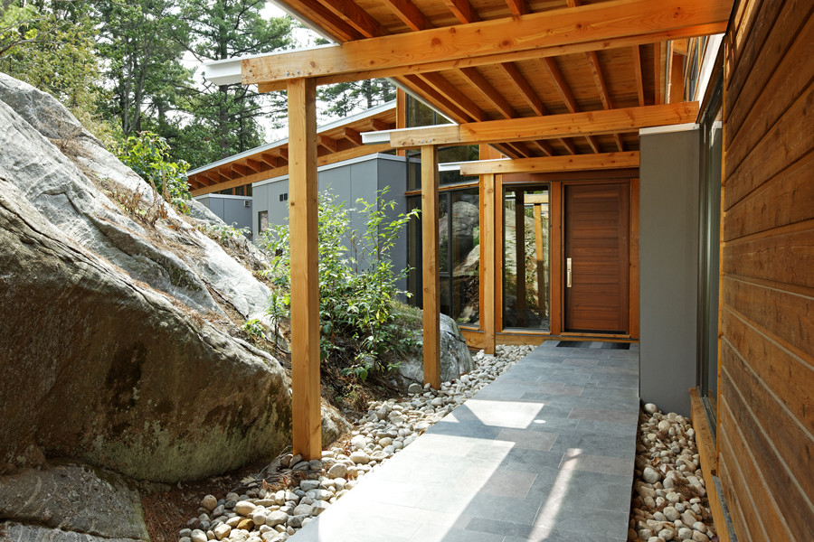 Covered walkway to front entrance with wood rafter cantilever roof with steel detail built into rock face