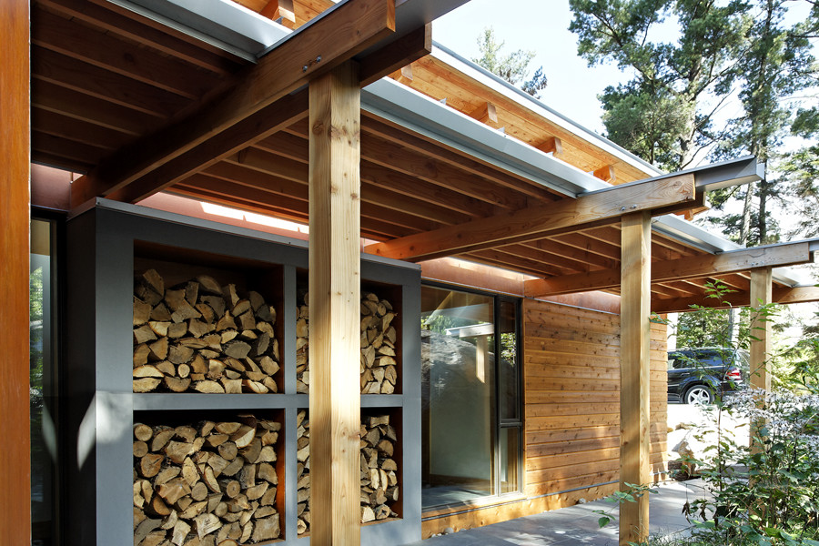 Covered walkway to front entrance with wood rafter cantilever roof with steel detail and firewood storage feature wall