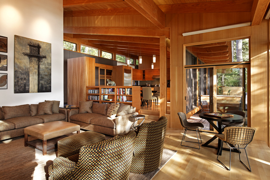 Living Room and kitchen with slanted wood rafter ceiling and clerestory windows on left and cantilever roof on right