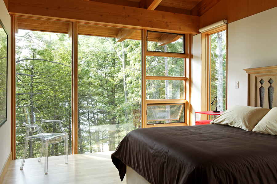 Bedroom with wood rafter ceiling with glazed wall looking through to trees