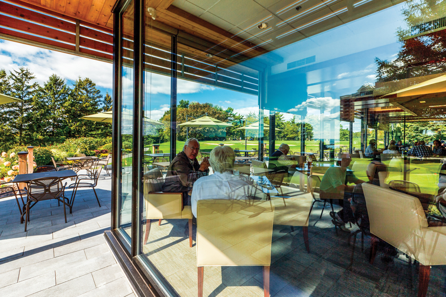 View of diners from patio through glass wall with golf course in the background