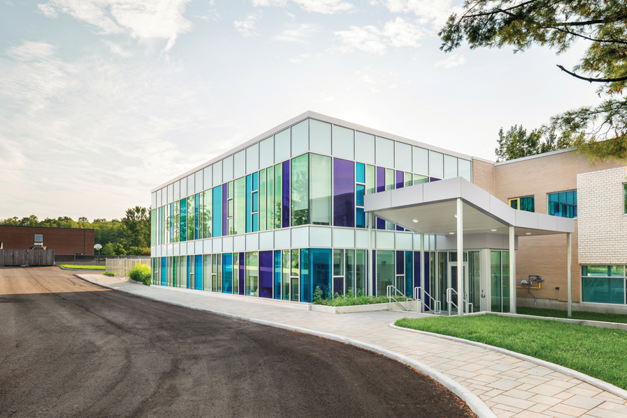 Front entrance of two storey school with scooped canopy and green, blue and purple tinted glass floor to ceiling windows on facade of building
