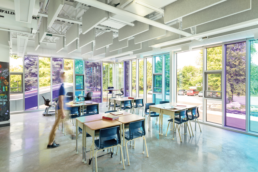 Classroom with flexible 4-desk pod seating and purple and blue tinted glass floor to ceiling windows