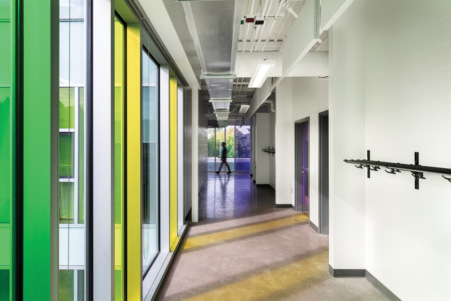 Classroom corridor with green and yellow tinted floor to ceiling windows on the left casting coloured shadows on the floor