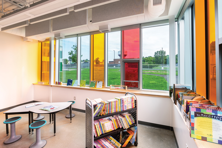 Reading room with stationary seating and moveable book shelf and orange and red tinted glass windows looking out to green field