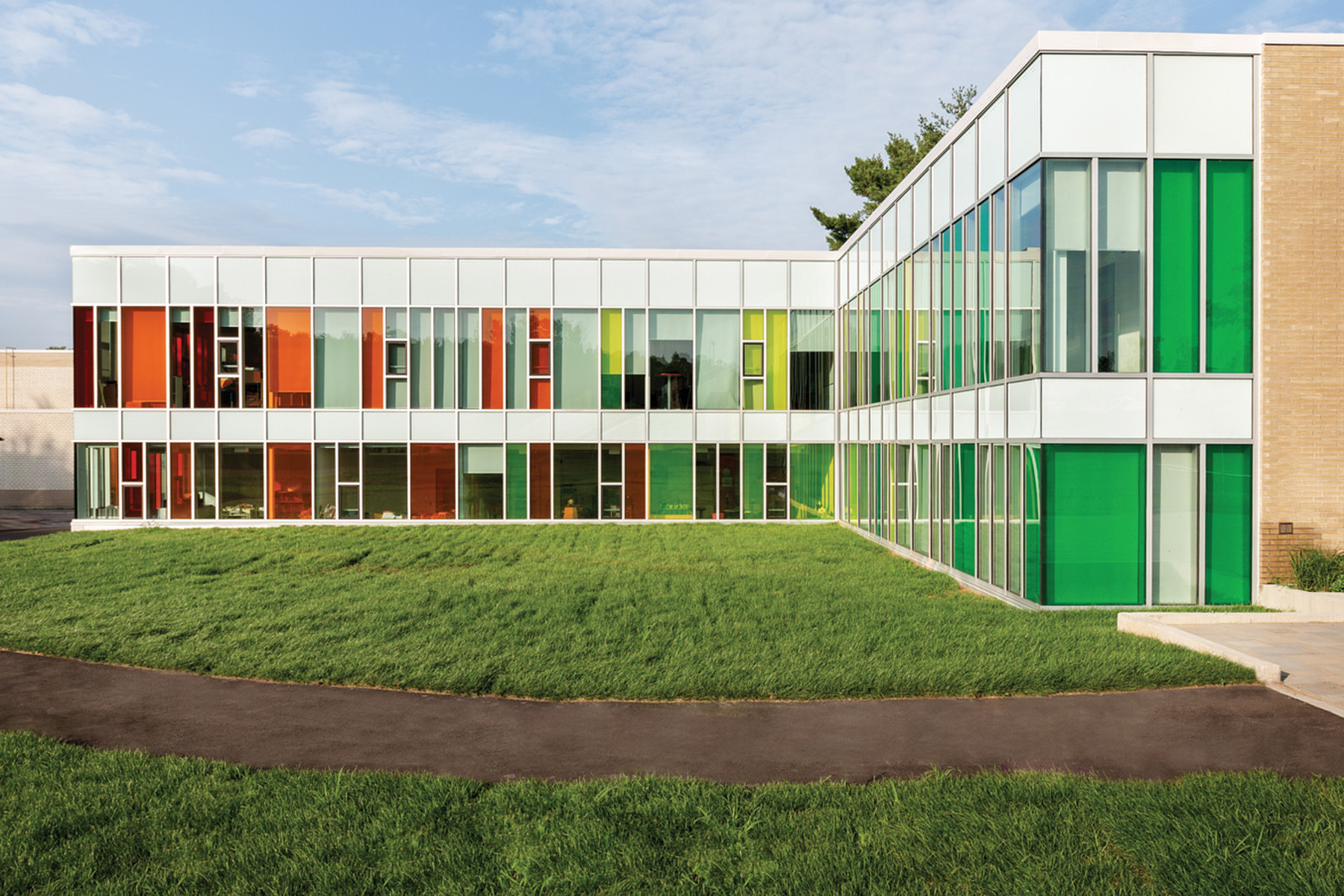 Back elevation of two storey school with orange, yellow and green tinted glass floor to ceiling windows