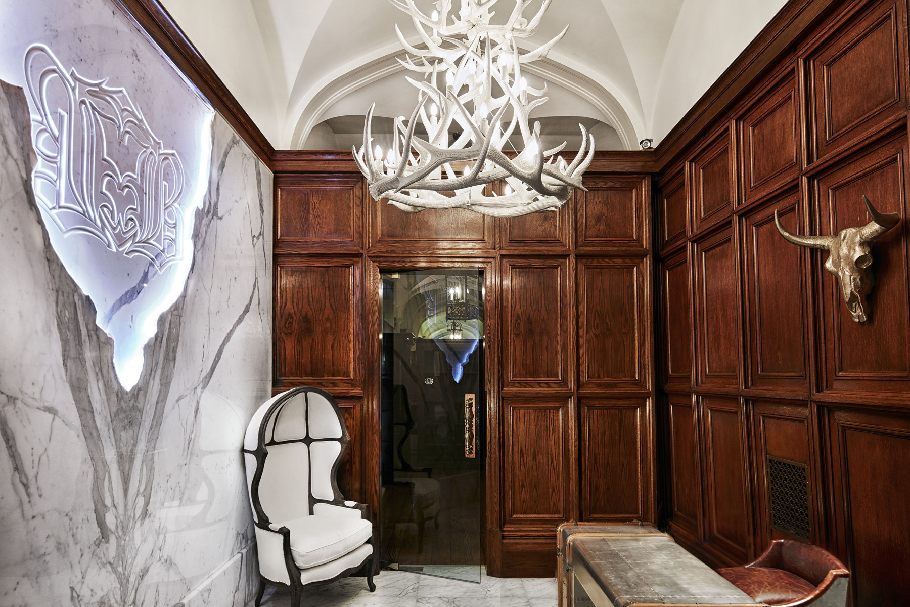 Corridor entrance with white antler chandelier, wood paneled walls with glass door and marble floors and feature wall with back lit logo