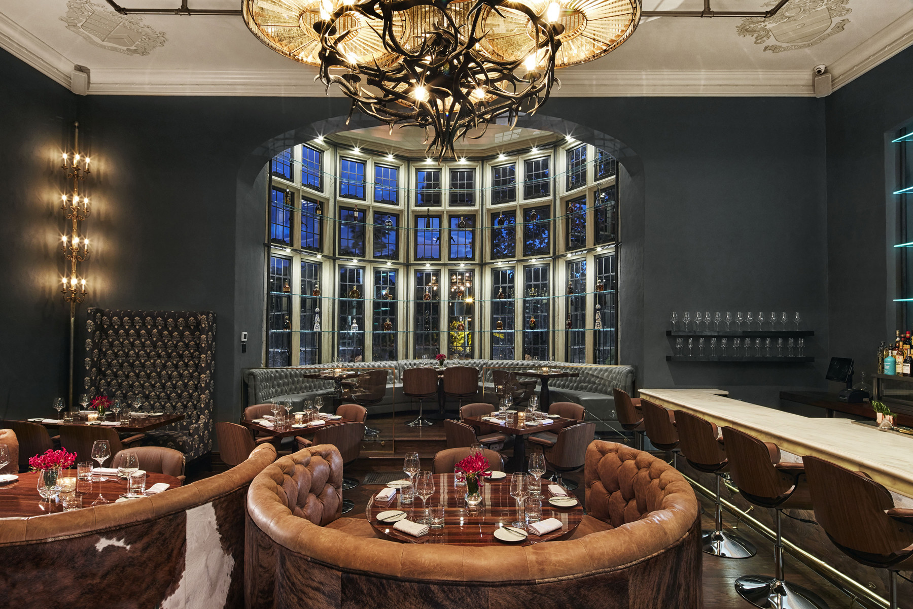 Central curved arched leaded glass window with banquet and leather semi-circle dining booths with bar seating on right