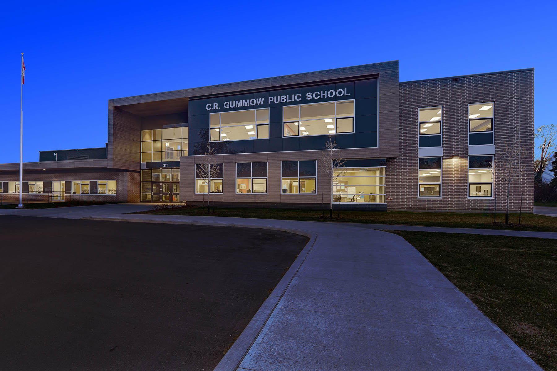 Illuminated view of front facade of school from entrance walkway at dusk