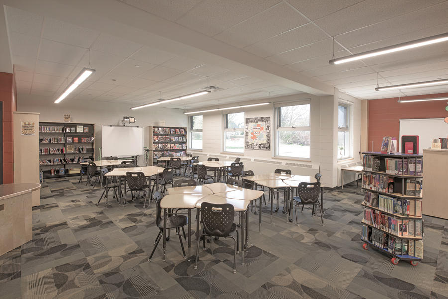 Resource Centre Library with flexible group seating and book shelves and red feature wall with white board on the right