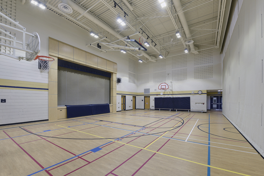 Gymnasium with basketball hoops and theatre stage on left