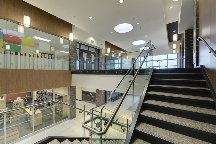 View of glazed Resource Centre Library on ground floor and lockers on second floor from open staircase in double height atrium