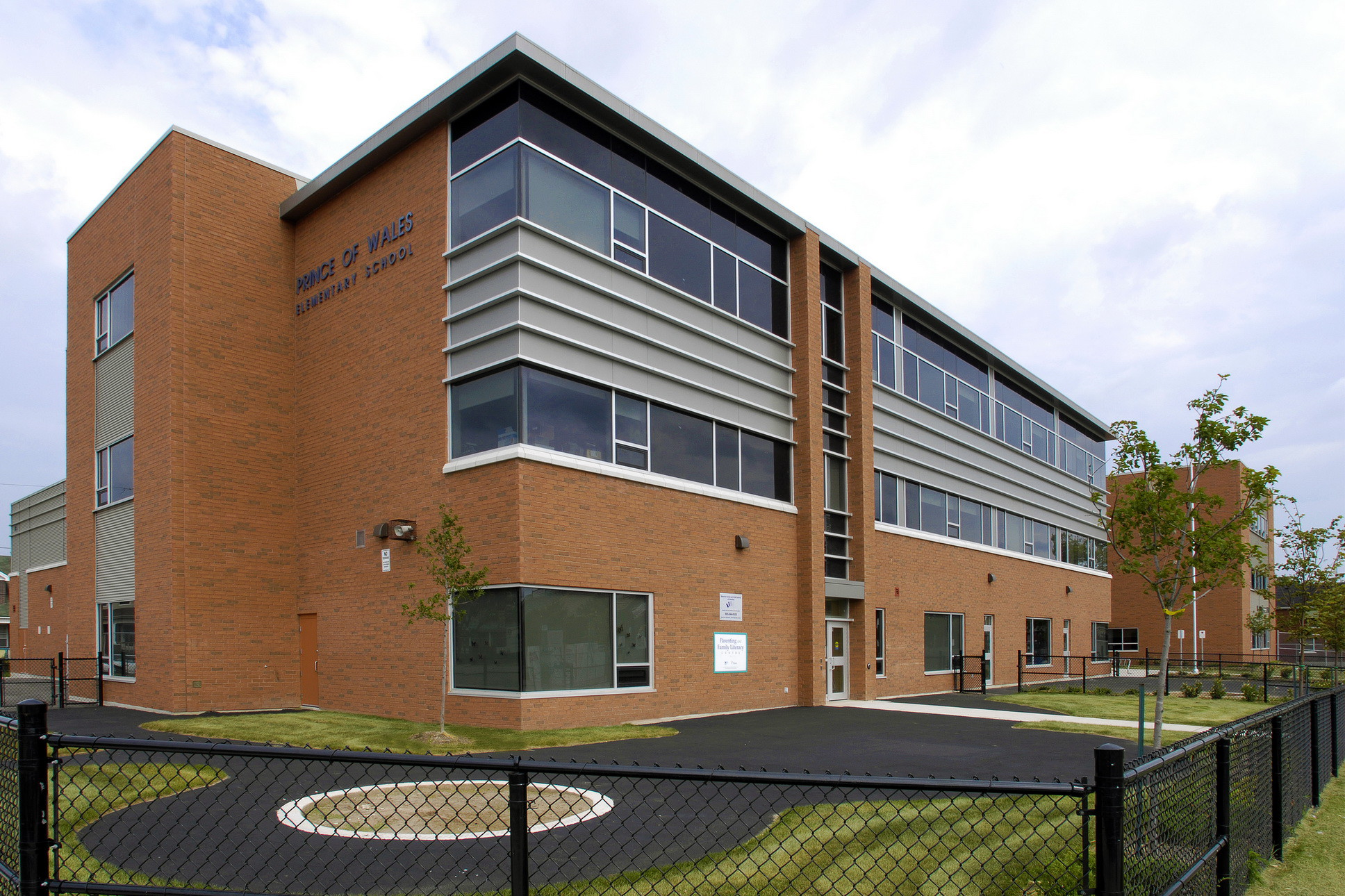 Red brick three storey school with windows and steel detail with fenced play area