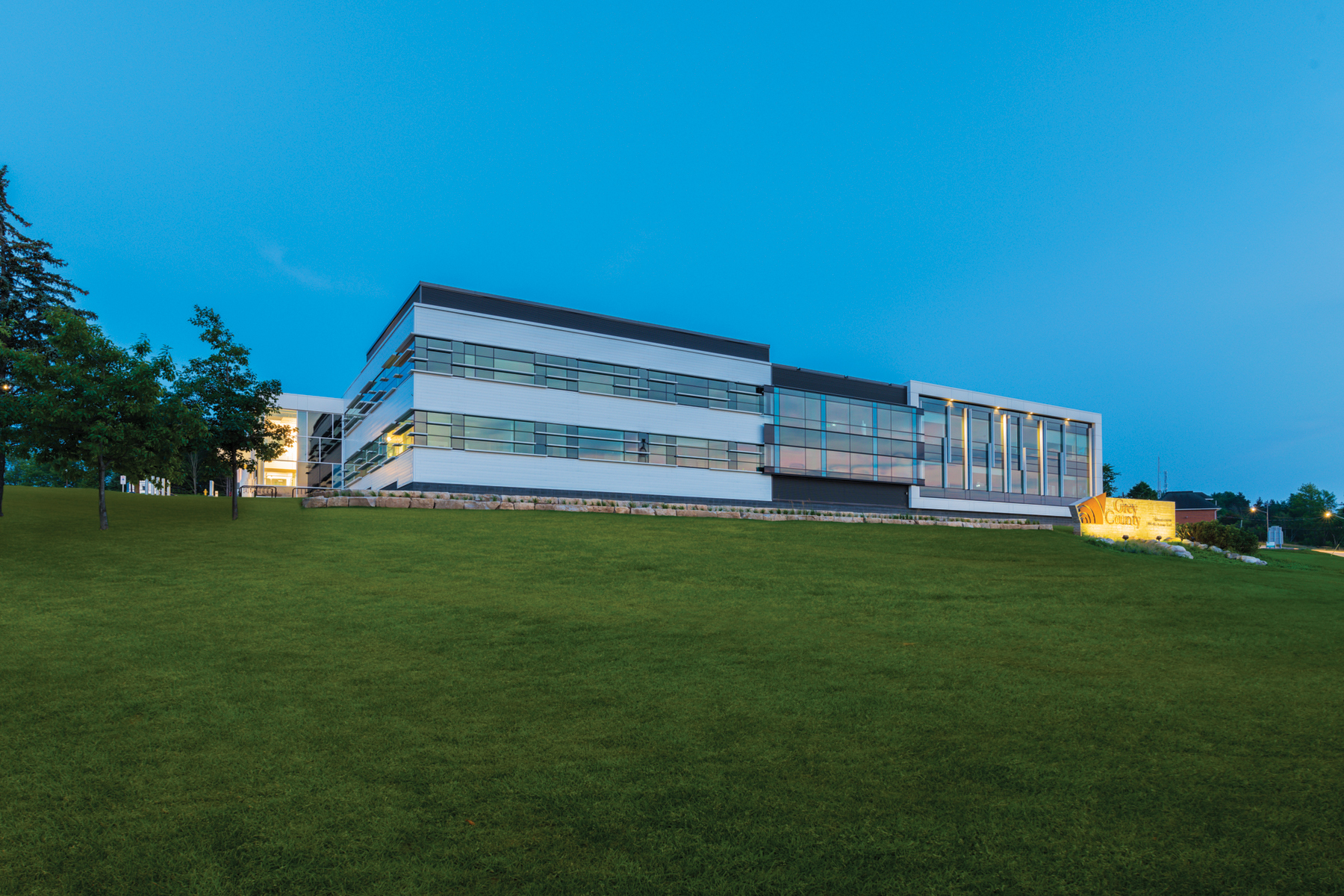 Elevation of glazed three storey building at dawn with blue sky and green grass