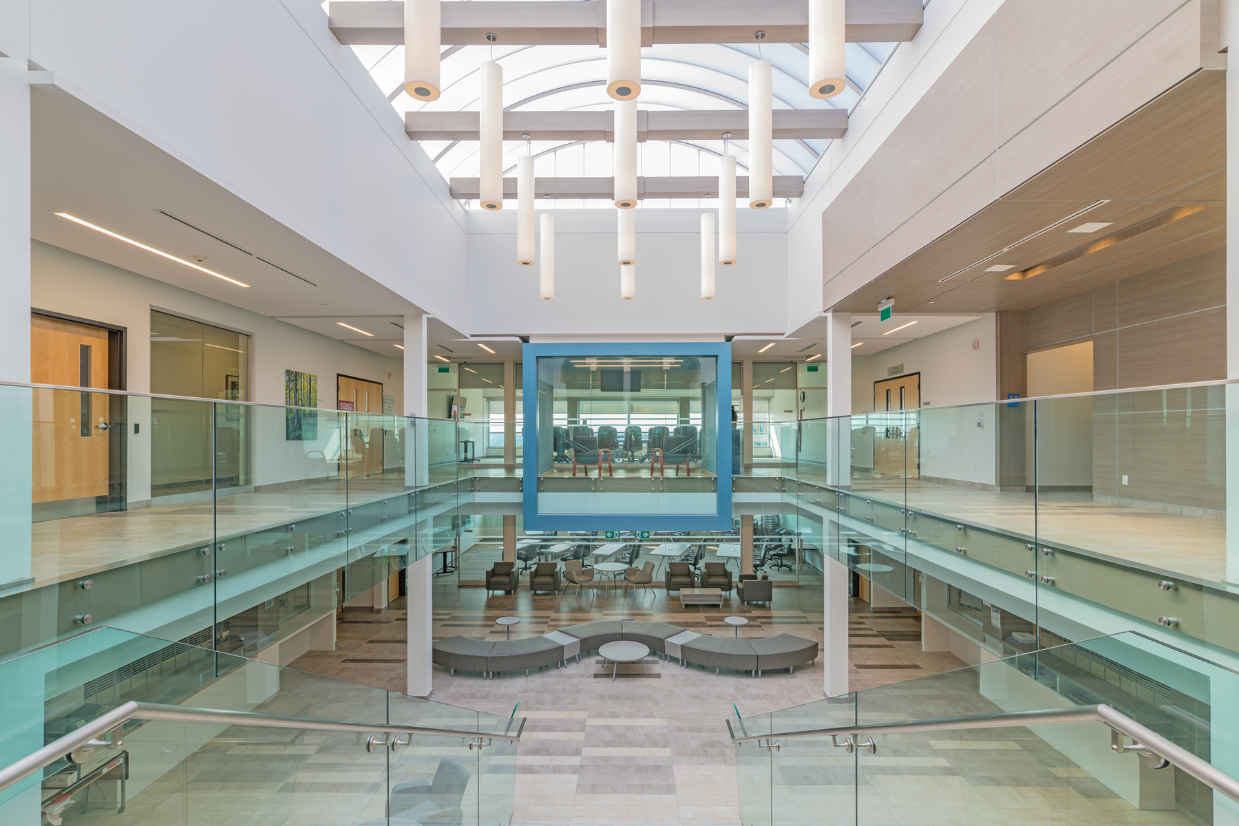 Central double height atrium space, with second storey perimeter corridors and blue framed glazed meeting room and seating on level below