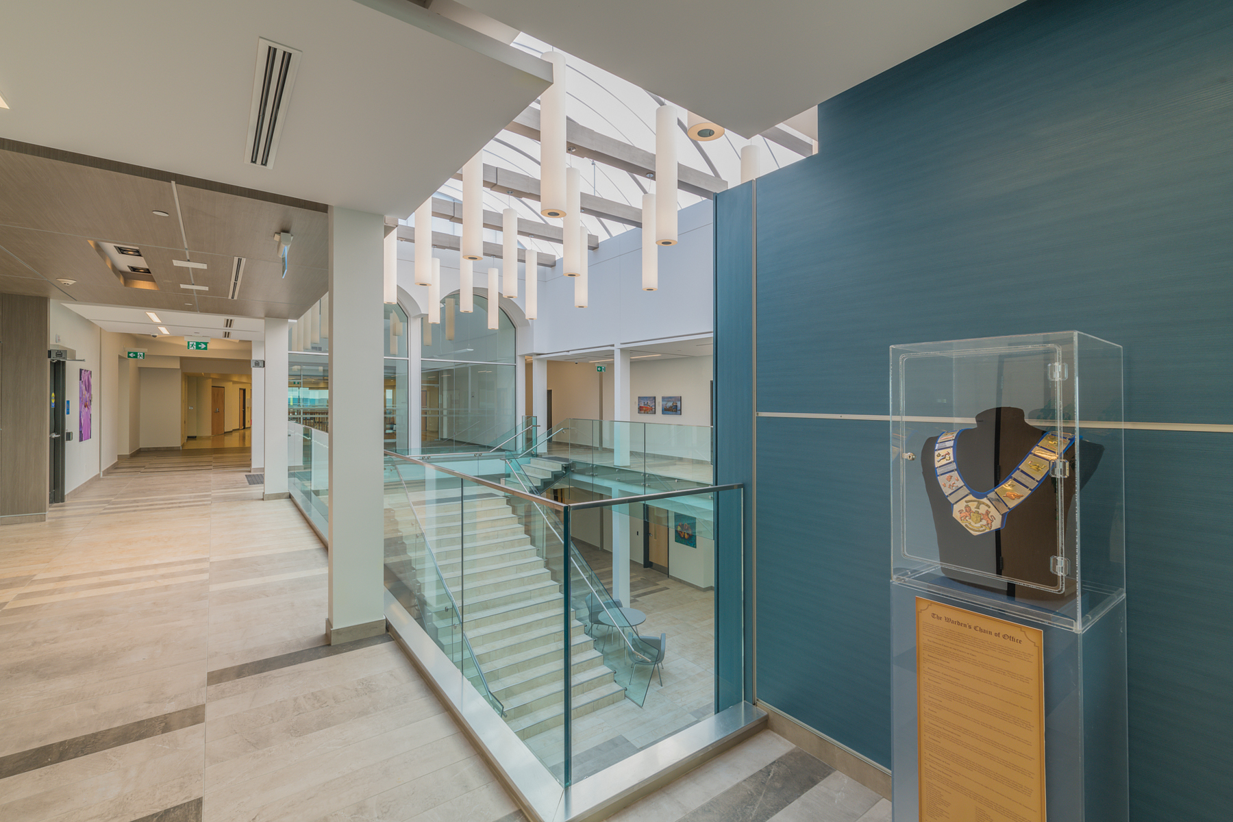 Second storey corridor with views of open staircase with skylights and white pendant lighting leading to ground floor level