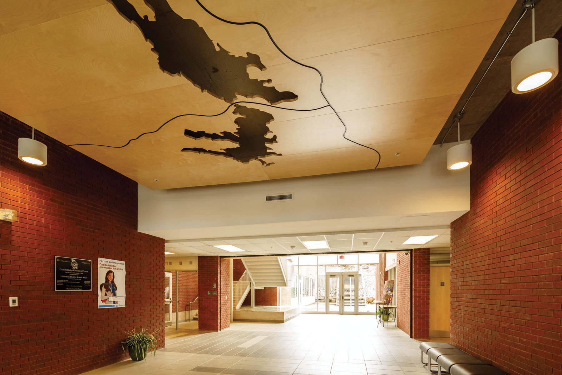 Main entrance lobby with exposed red brick walls and wooden lakes cut out feature ceiling