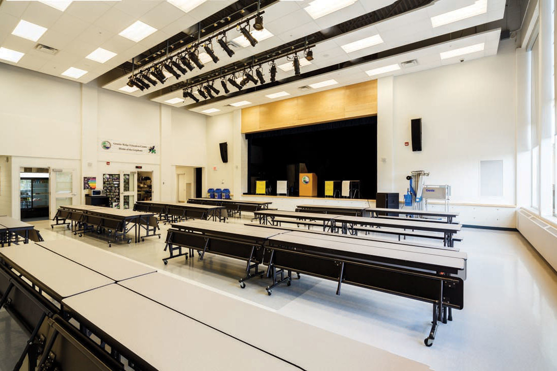 Cafeteria with stage and ceiling mounted theatre lighting and large bright windows on right overlooking green space