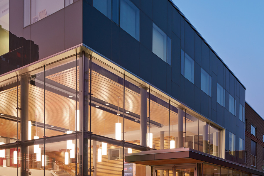 Front entrance to illuminated double height student commons with cantilever at dusk