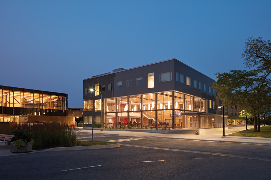 View of building from across the street featuring illuminated double height student commons at dusk