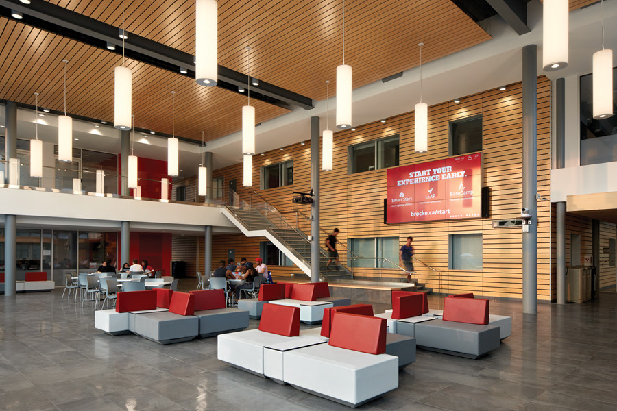 Double height student commons with glazed second storey corridor, wood paneling on walls and ceiling and white and red lounge seating