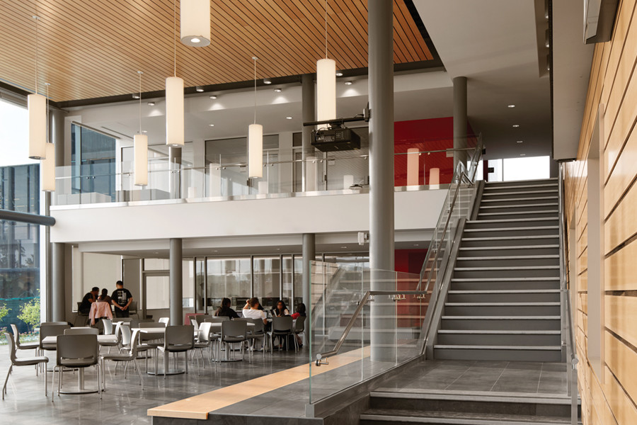 Staircase to second storey from double height student commons with wood plank ceiling and white pendant lighting
