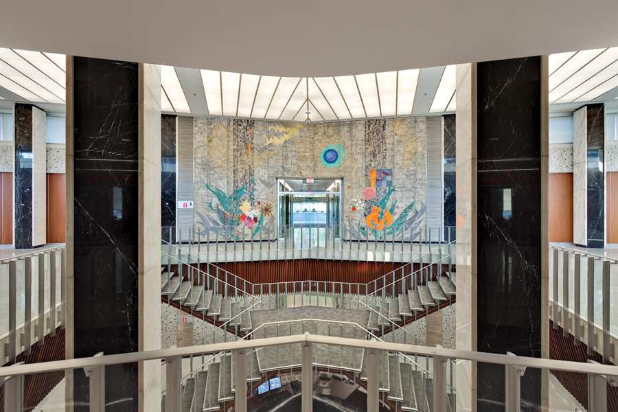 View from second storey of entrance lobby featuring large floor to ceiling colourful wall mosaic and staircases connecting multiple levels