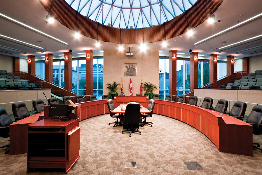 Council chamber with semi circle council person seating and public gallery seating behind, and large leaded glass dome skylight above