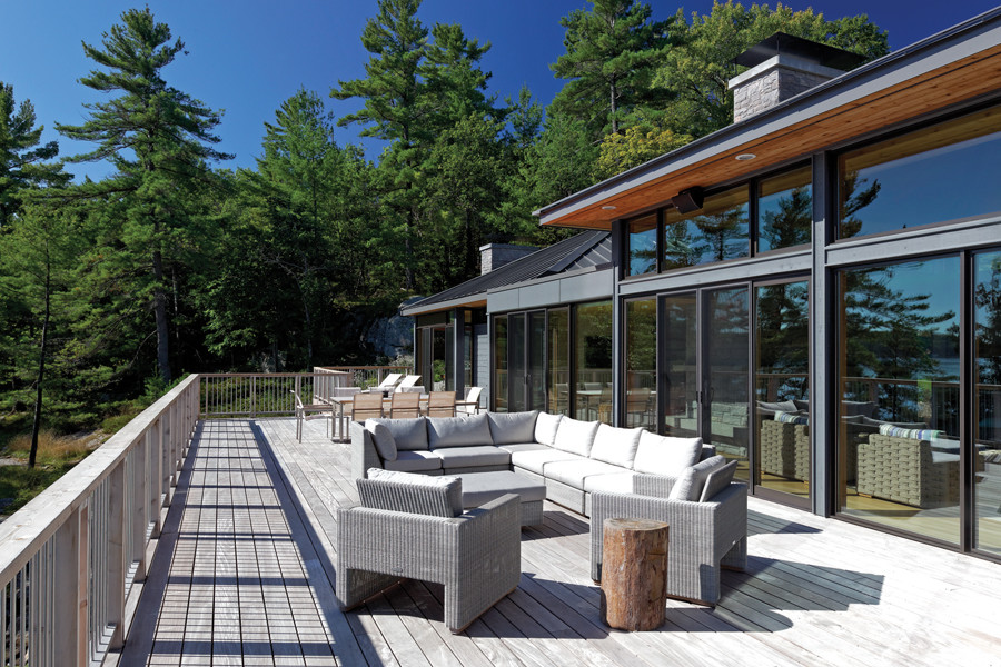 Tree lined large upper outdoor patio with ample seating looking through glazed wall into living room on a sunny day