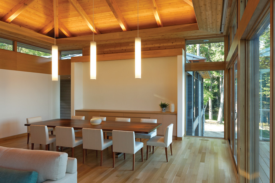 Dining room with exposed wood rafter ceiling and white pendant lighting, clerestory windows and glazed walls with view of trees