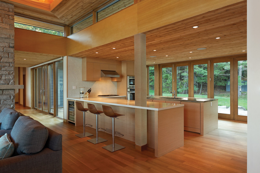 Kitchen with millwork ceiling and paneled glass doors and clerestory windows with views of trees