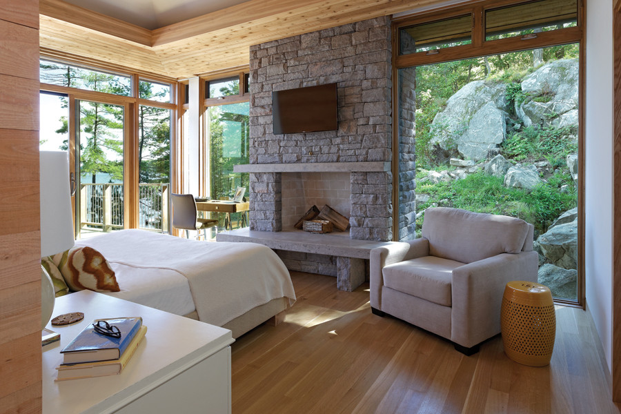 Bedroom with stone floor to ceiling fireplace and views of lake, trees and rock face from large glazed windows
