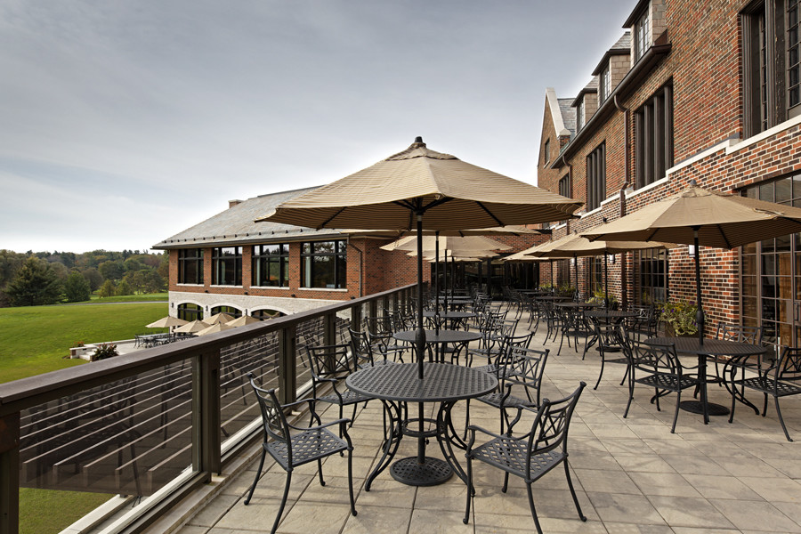 Outdoor patio seating with cast iron tables and chairs and umbrellas on second level overlooking ground floor patio seating and golf course