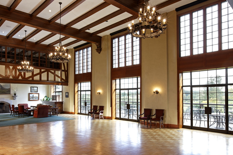 Double height banquet space with large chandeliers, exposed rafter ceiling and leaded glass windows with views to outdoor patio