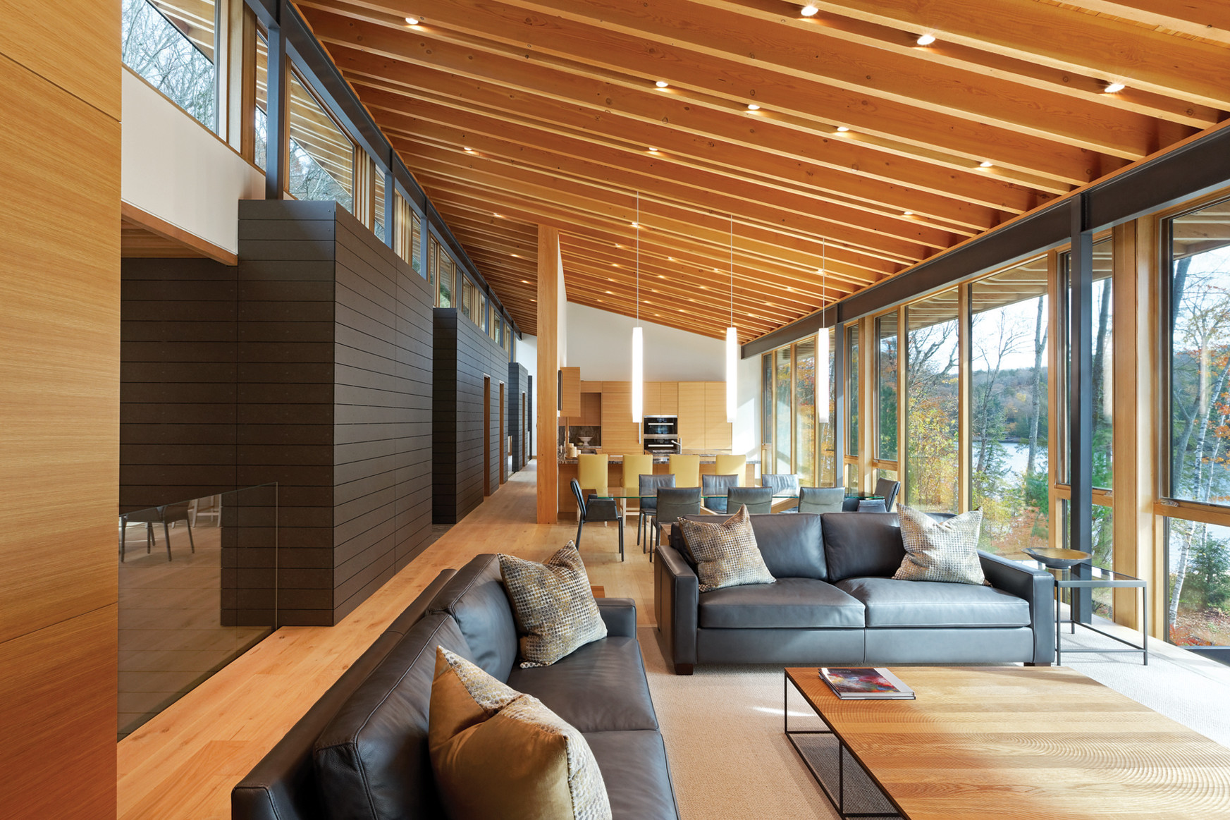 Open concept living room, dining area and kitchen with slanted rafter ceiling with clerestory windows and glazed wall with views of lake and trees