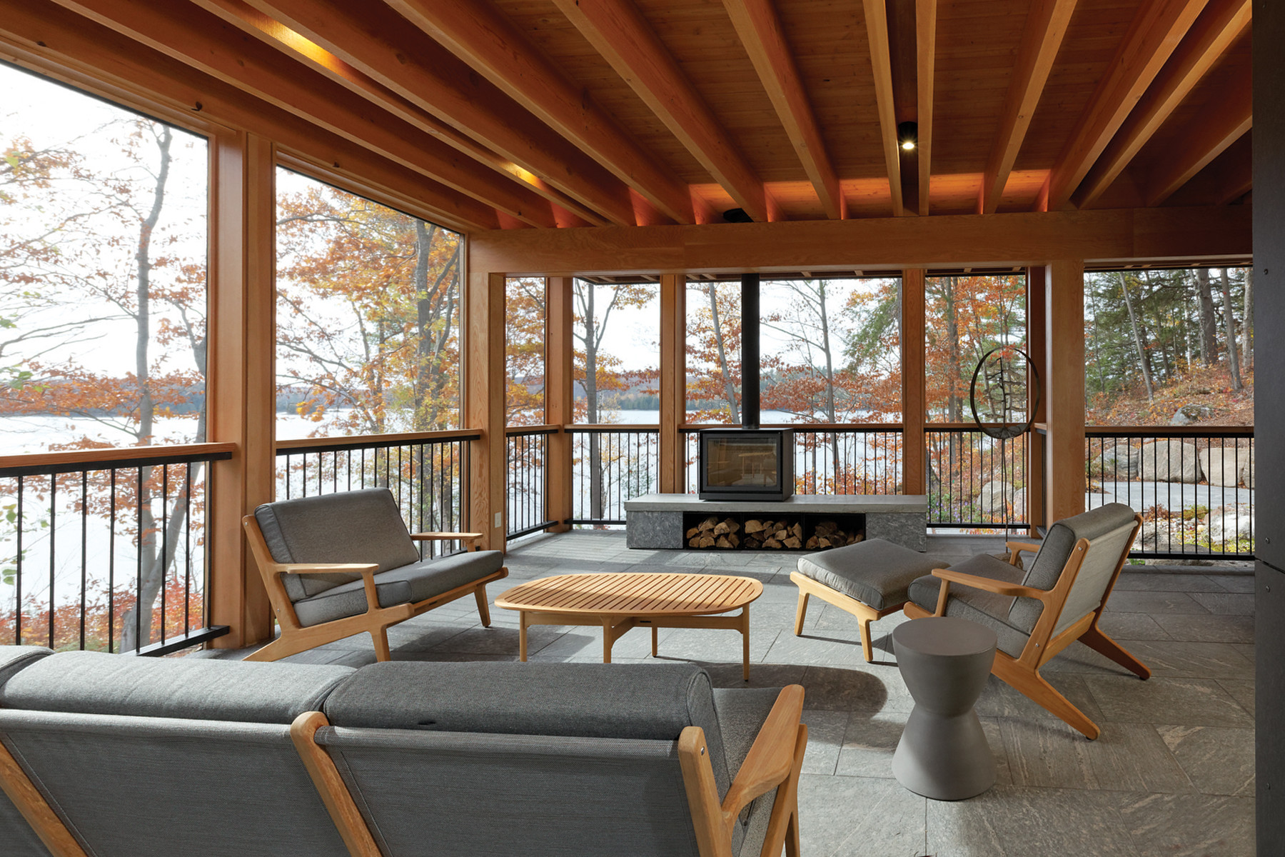Screened porch with seating, fire place and wood rafter ceiling with wrap around views of trees and lake