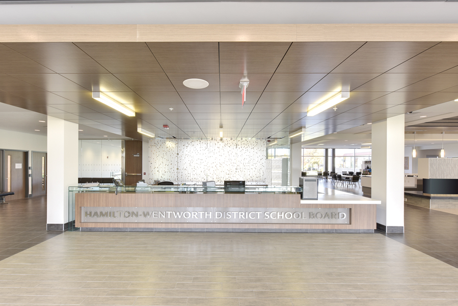 Large reception desk with Hamilton-Wentworth District School Board lettering, flanked by white columns with wood panel ceiling