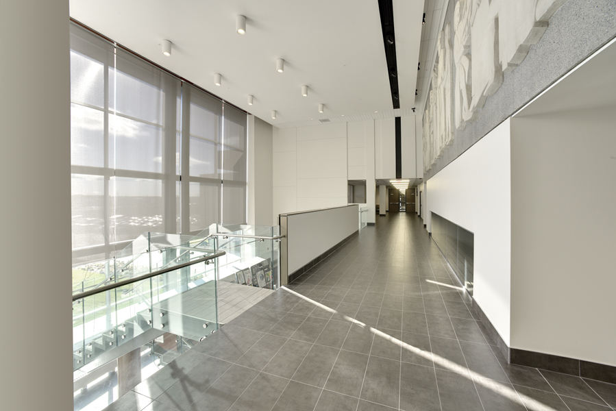 View of bright white second storey corridor from top of feature stair with glass guard rail and glazed double height wall on left