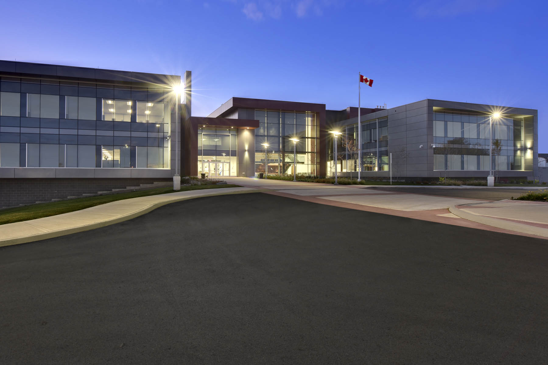View from parking lot of illuminated two storey building with lamp posts and Canadian flag at dusk