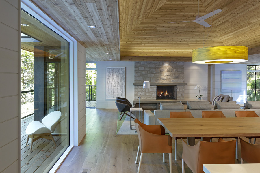 Open concept dining area and living room featuring floor to ceiling stone fireplace and wood tiered ceiling